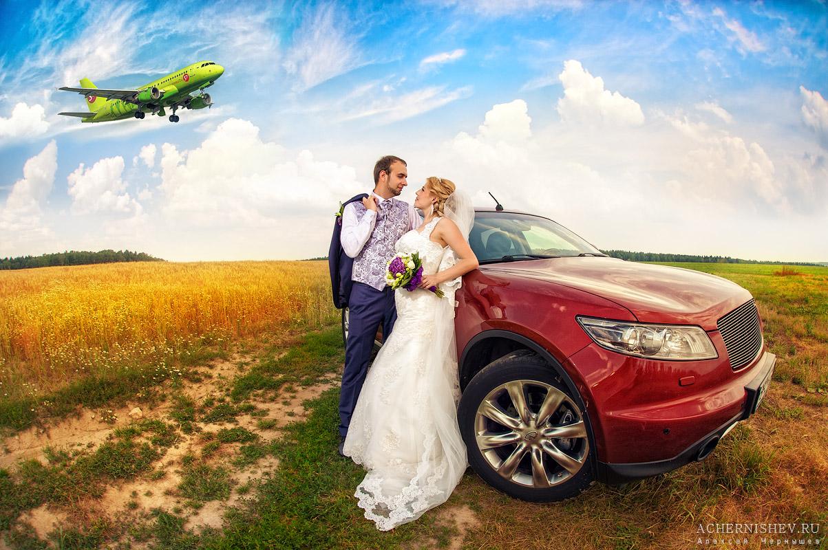 фотография в поле с машиной и самолетом на заднем плане