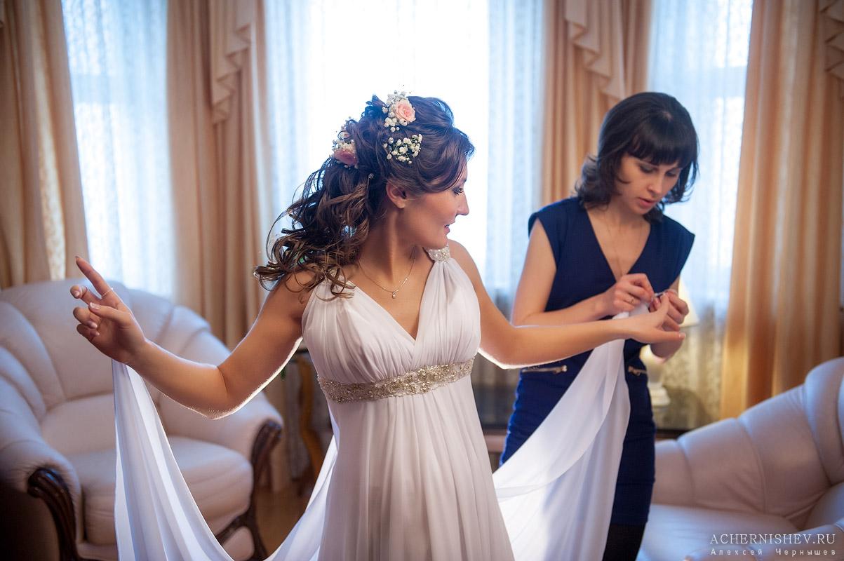 подружка помогает одеть подвенечное платье